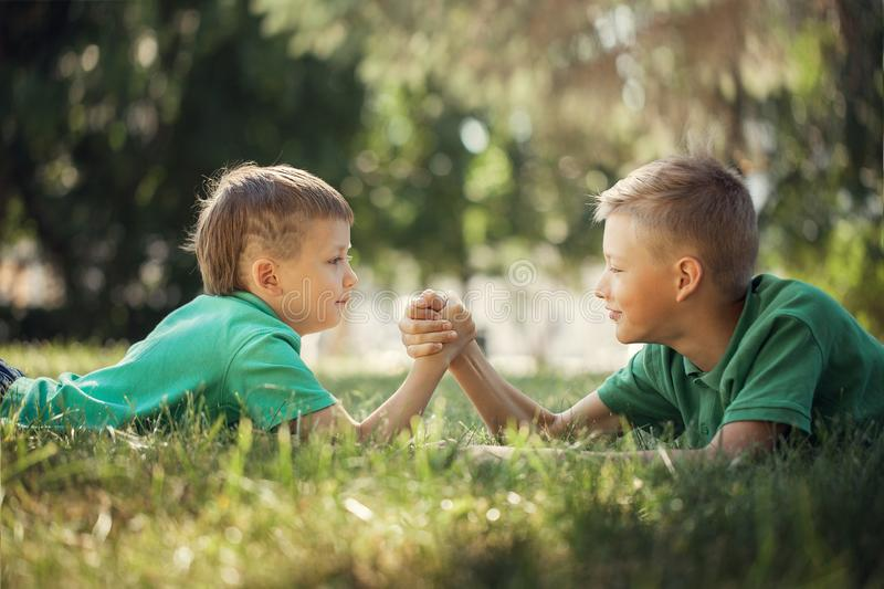 Two boys clasped hands engaged in an arm wrestle on green lawn in summer. Day stock image