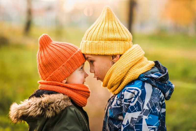 Two boys in colored hats stand opposite each other royalty free stock photo