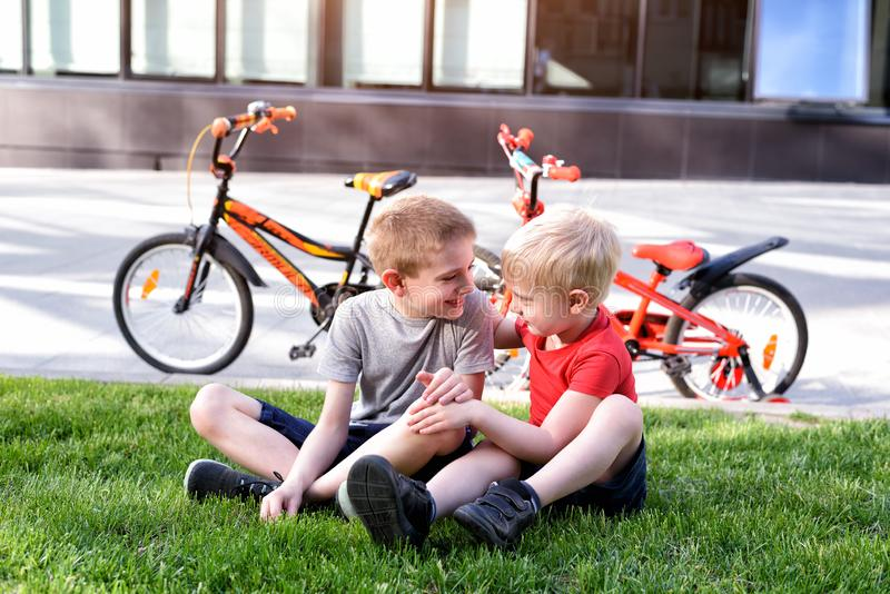 Two boys communicate sitting on the grass. Rest after cycling, bicycles in the background royalty free stock photography