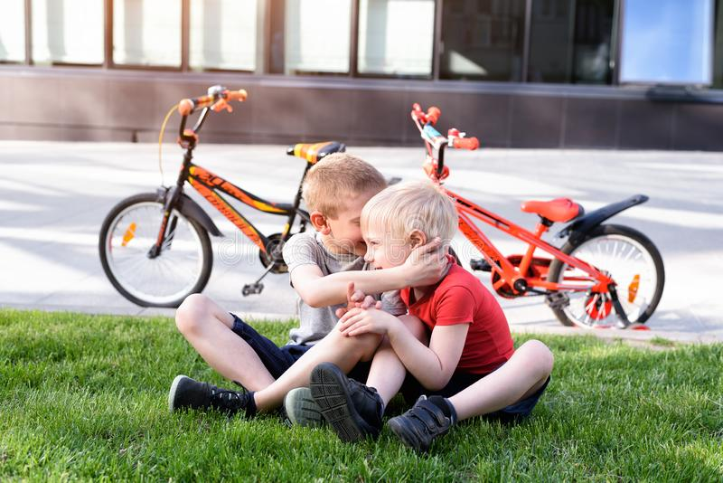 Two boys communicate sitting on the grass. Rest after cycling, bicycles in the background royalty free stock photo