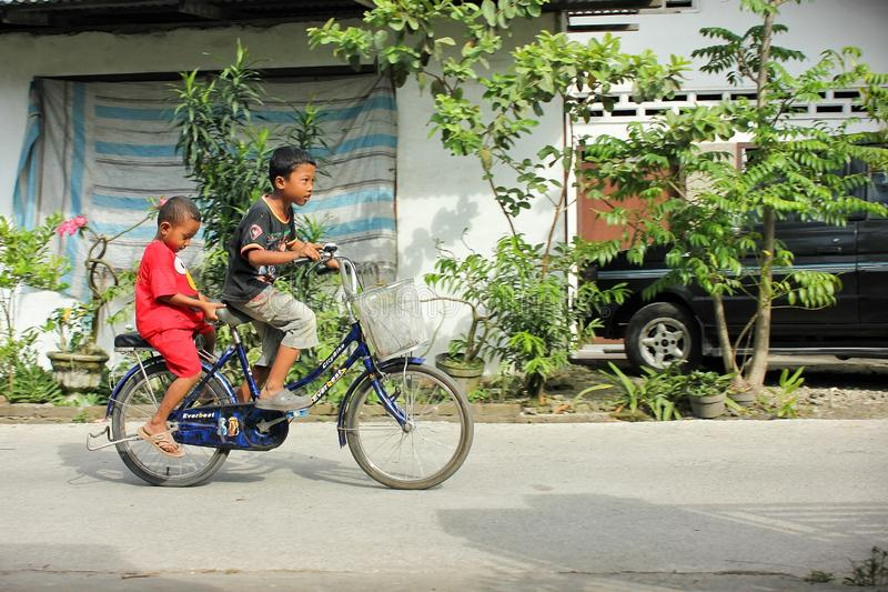 Two boys cycling. On a residential alleyway royalty free stock image