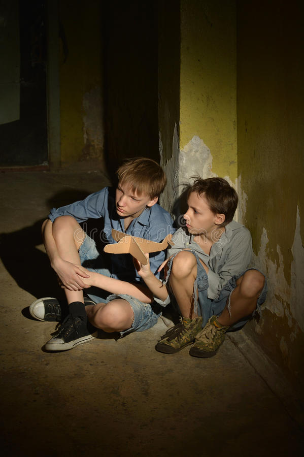 Two boys in a dark basement stock images
