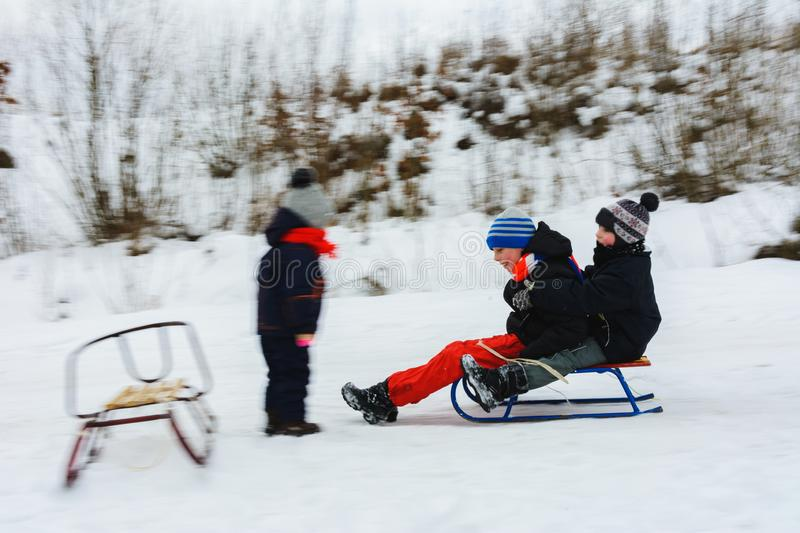 The two boys descend on sledges, and the girl waits for them, their movement is visible royalty free stock images