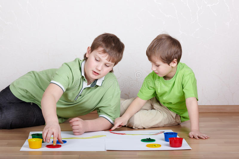 Two boys draw paints on sheets of paper stock photo