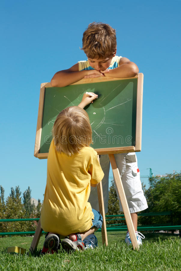 Two boys drawing outdoor. Two boys drawing on fresh air stock image