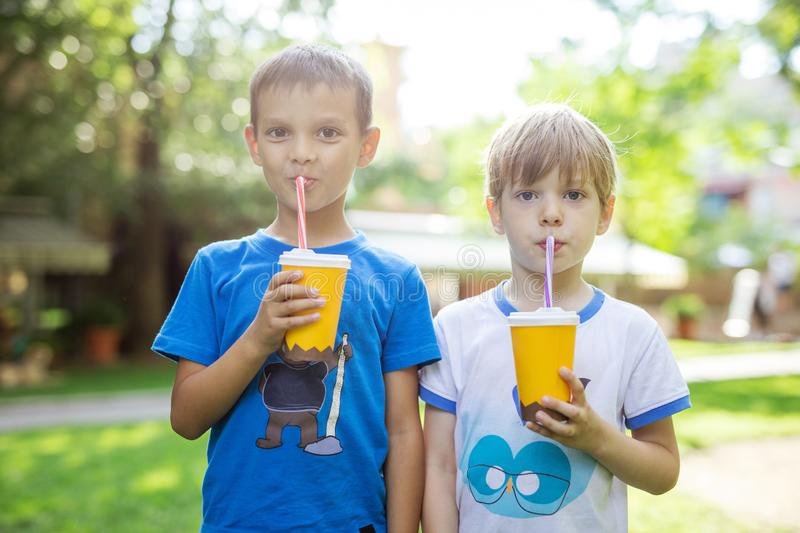 Two boys drinking cocoa from paper cups with straws in park. Two boys drinking cocoa from paper cups with straws in summer park stock photos