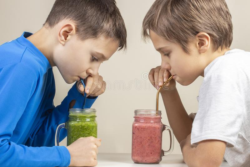 Two boys drinking healthy smoothie cocktail at home royalty free stock photos