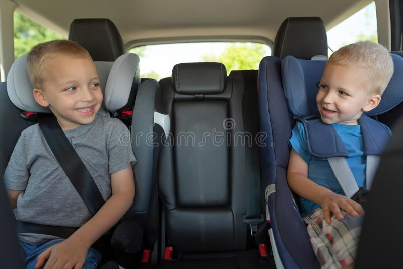 Two boys are driving in car seats. Safety of children while traveling by car royalty free stock image