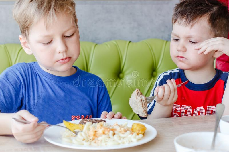Two boys eating pasta with a cutlet. Two little boys eating pasta with a cutlet from one plate royalty free stock photos