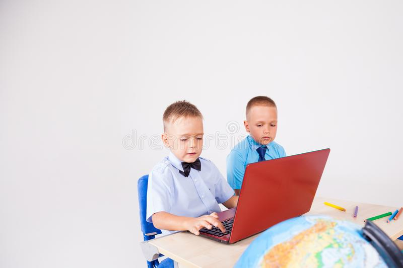 Two boys sit at the computer training school royalty free stock photos