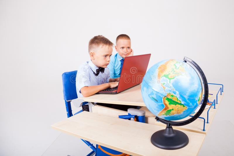 Two boys sit at the computer training school royalty free stock photo
