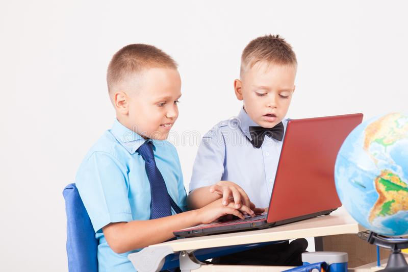 Two boys sit at the computer training school stock images