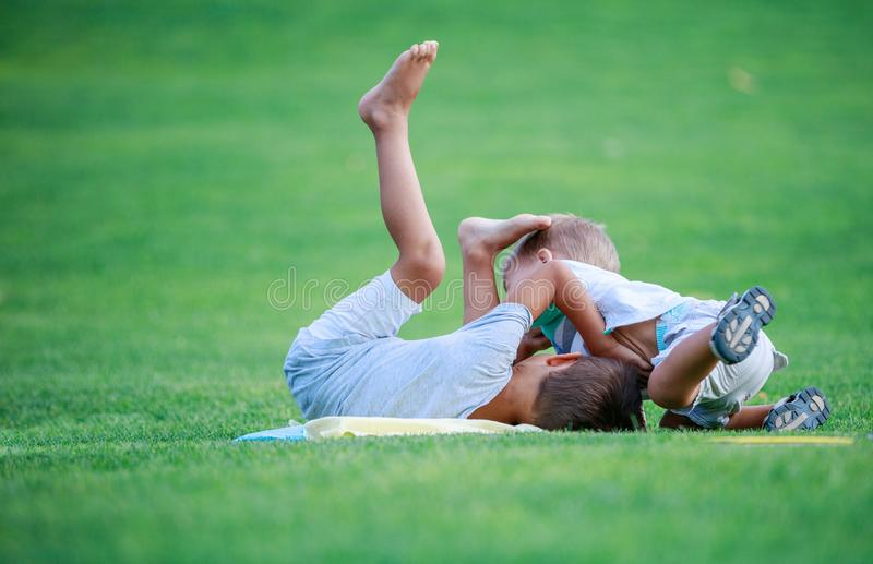 Two boys fighting outdoors. Siblings wrestling on grass in park stock photo