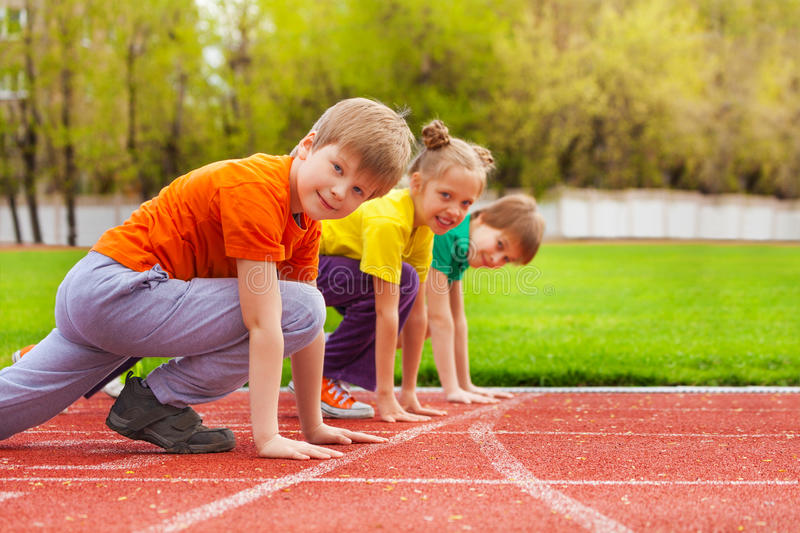 Two boys and girl stand on knee ready to run stock photo