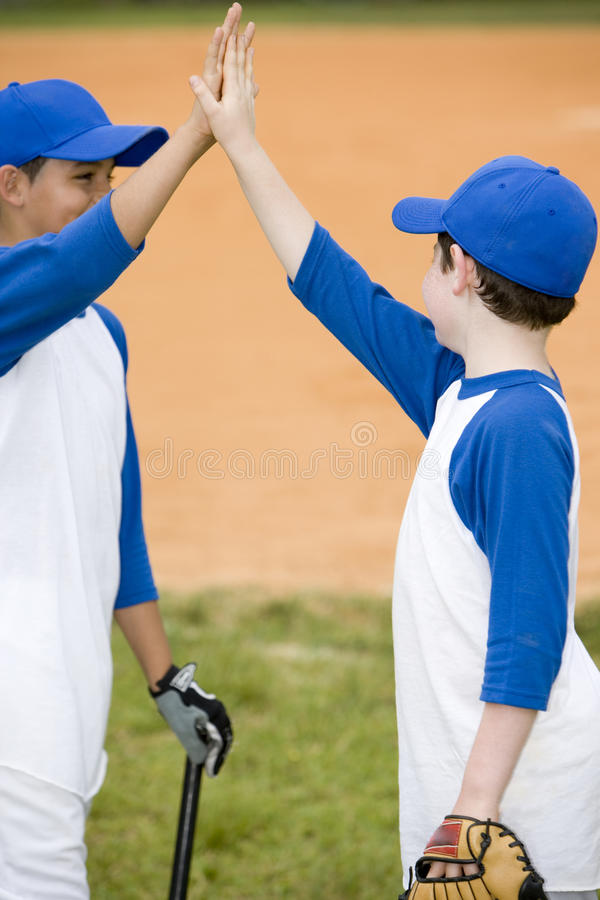 two boys giving a high five at baseball match royalty free stock photo