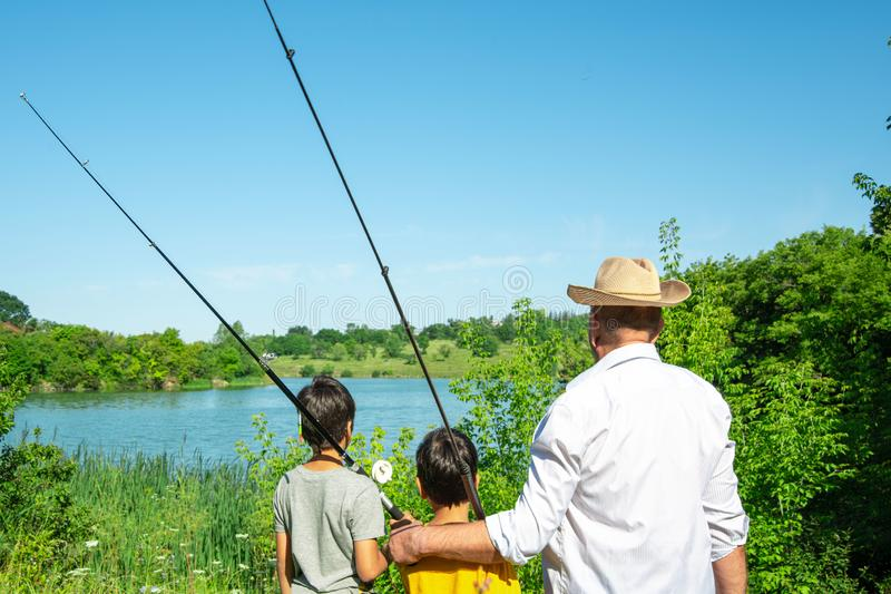 Two boys and grandfathers went fishing.  They stand on the shore of the pond and look into the distance stock photography