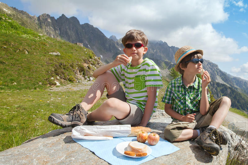 Two boys have picnic on stone in Alps royalty free stock photos