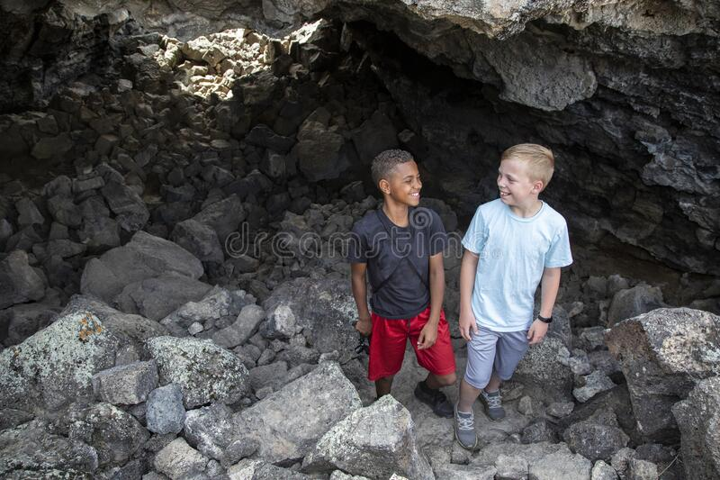 Two boys having fun hiking and exploring in some Lava rock caves stock photos