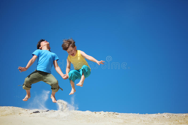 Download Two boys jump on sand stock photo. Image of outdoor, hold - 10503604