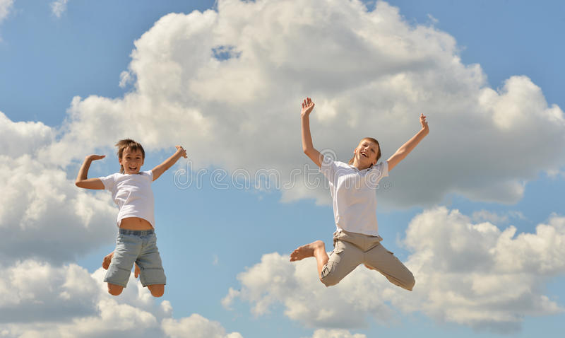 Two boys jumping. On a sky background royalty free stock images