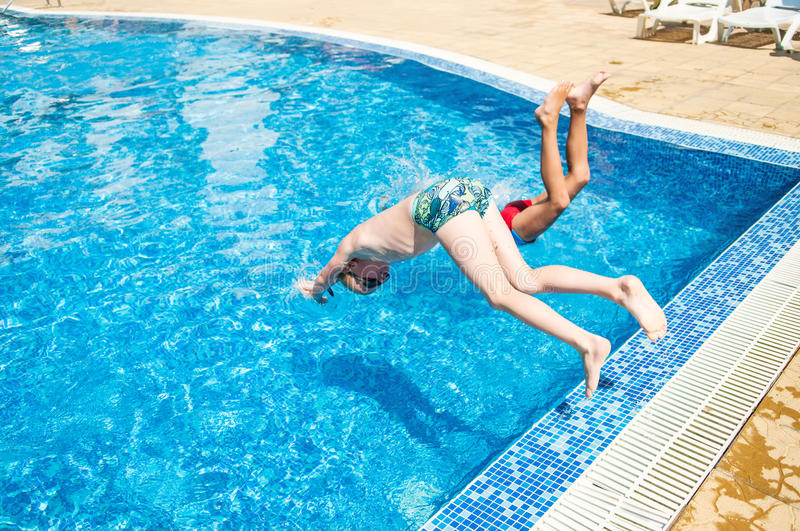 Two boys jumping into swimming pool royalty free stock images