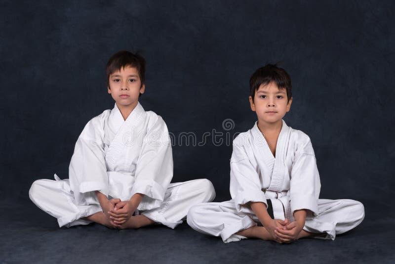 Two boys of the karate in a white kimono stock photography