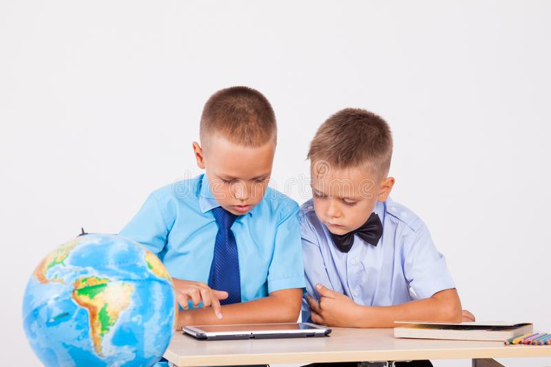 The two boys are looking at Internet Tablet school stock photos