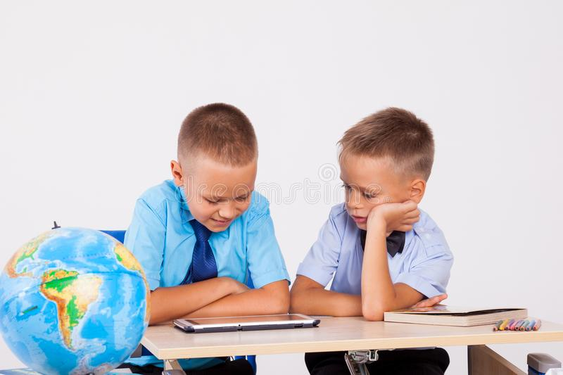 The two boys are looking at Internet Tablet school stock photo