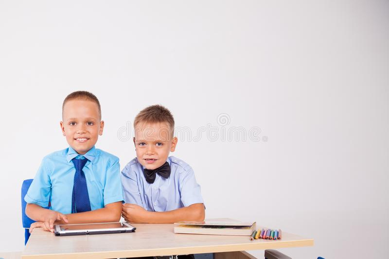 The two boys are looking at Internet Tablet school royalty free stock photo