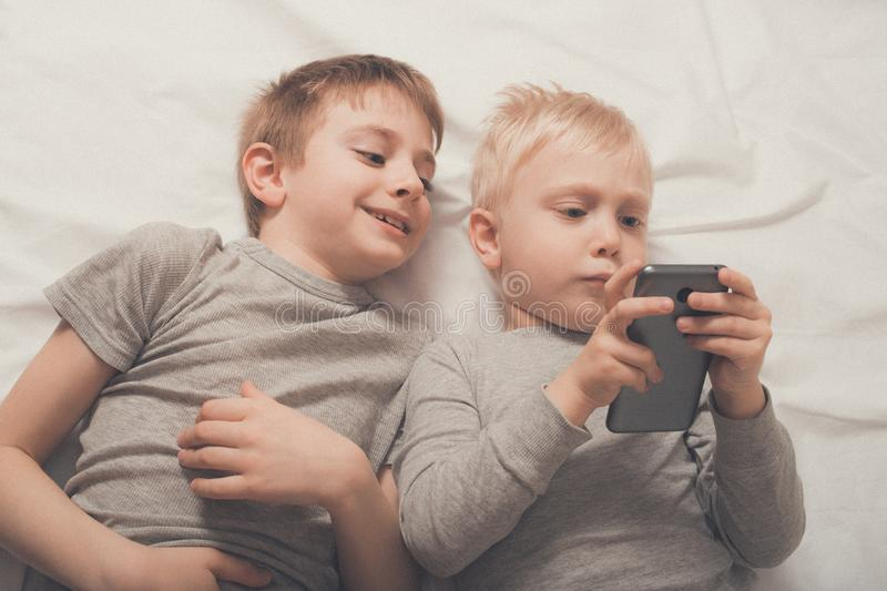 Two boys are lying in bed with a smartphone. Gadget Leisure stock photo