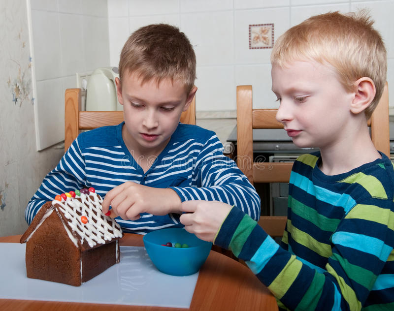 Two boys making gingerbread house stock photos
