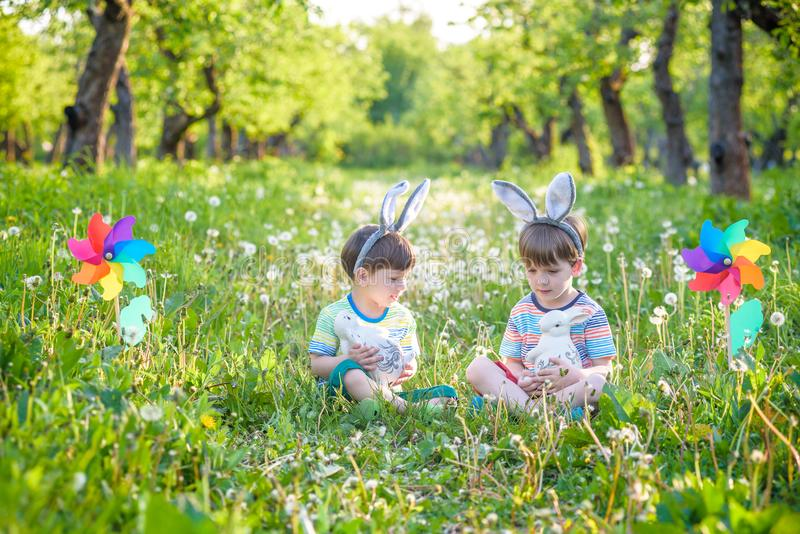 Two boys in the park, having fun with colored eggs for Easter stock images