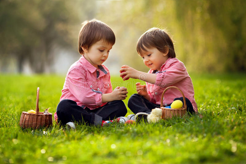 Two boys in the park, having fun with eggs for Easter royalty free stock photography