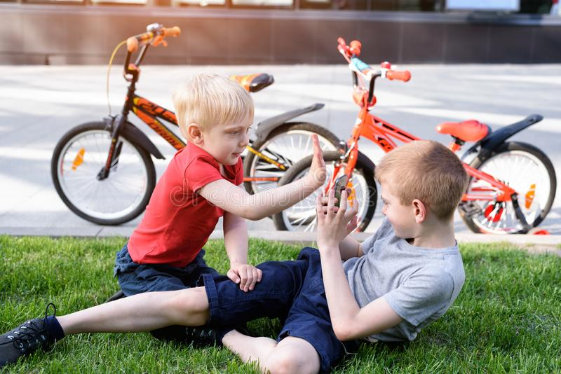 Two boys are photographed on a smartphone while sitting on the grass. Rest after cycling, bicycles in the background.  stock photos