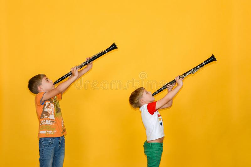 Two boys play the clarinet and hold it up, on a yellow background stock photos