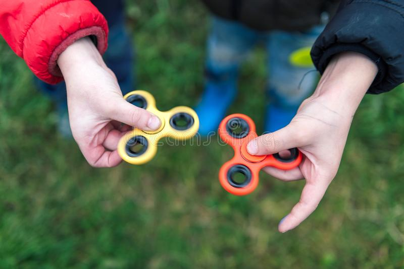 Two boys playing fidget spinners. Outdoor. stock photography
