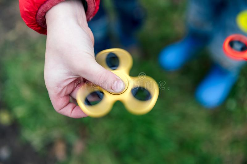 Two boys playing fidget spinners. Outdoor. stock photos