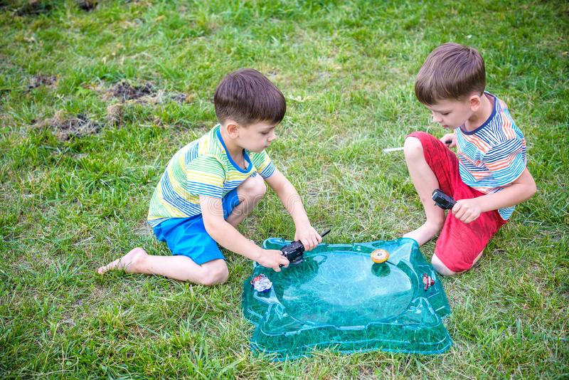 Two boys playing with a spinning top kid toy. Popular children game tournament royalty free stock photos