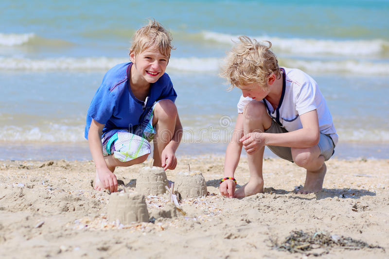 Two boys playing with sand on the beach stock images