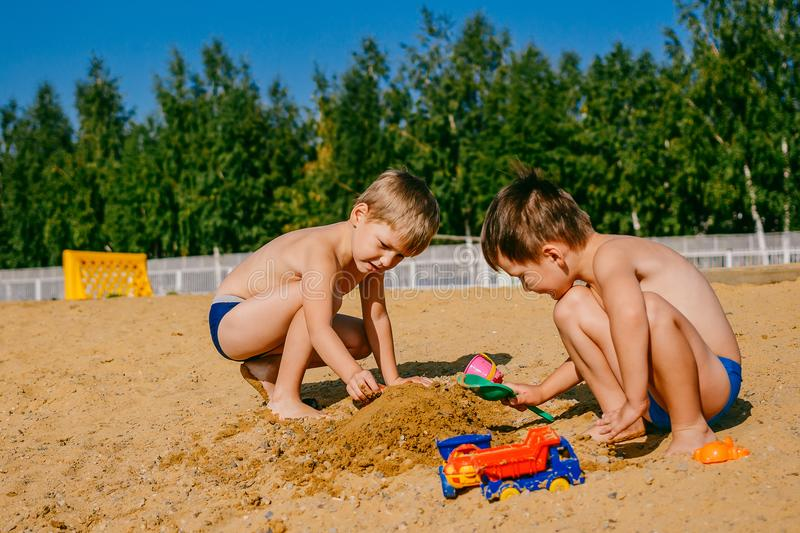 Two boys playing in the sand stock photo