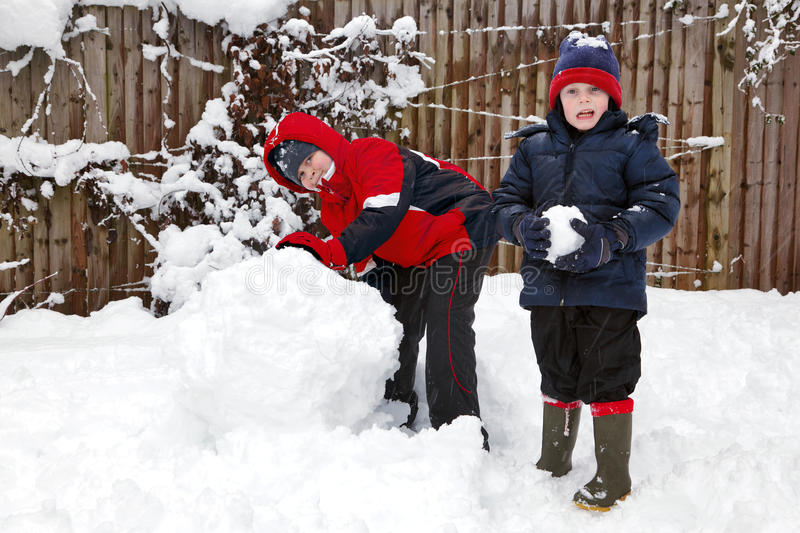 Two boys playing in the snow royalty free stock image