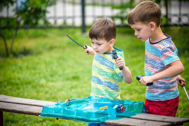 Two boys playing with a spinning top kid toy. Popular children game stock images