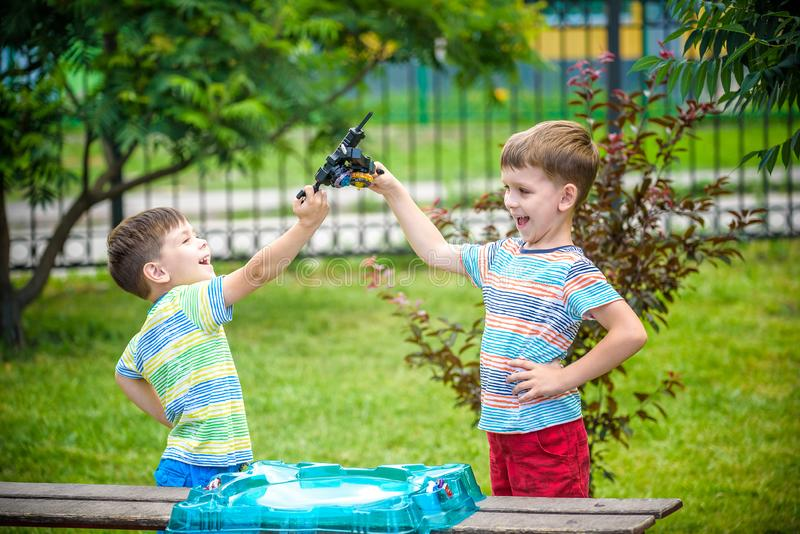 Two boys playing with a spinning top kid toy. Popular children game royalty free stock images