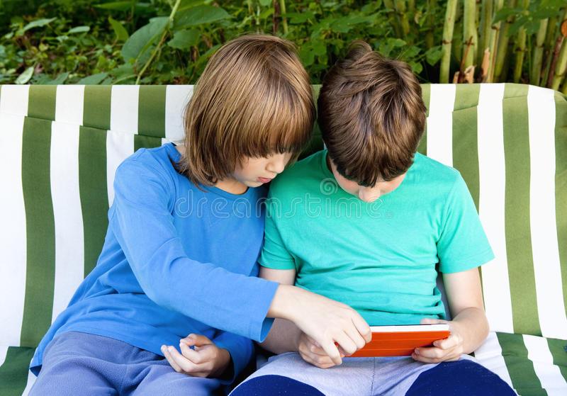 Two Boys Playing with Tablet stock images