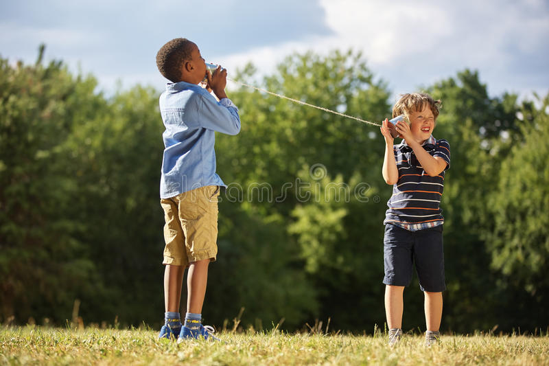 Two boys playing tin can telephone stock images