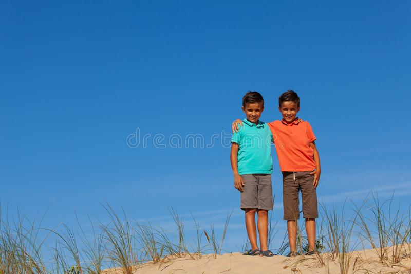 Two boys portrait hugging standing on a sand dune stock image