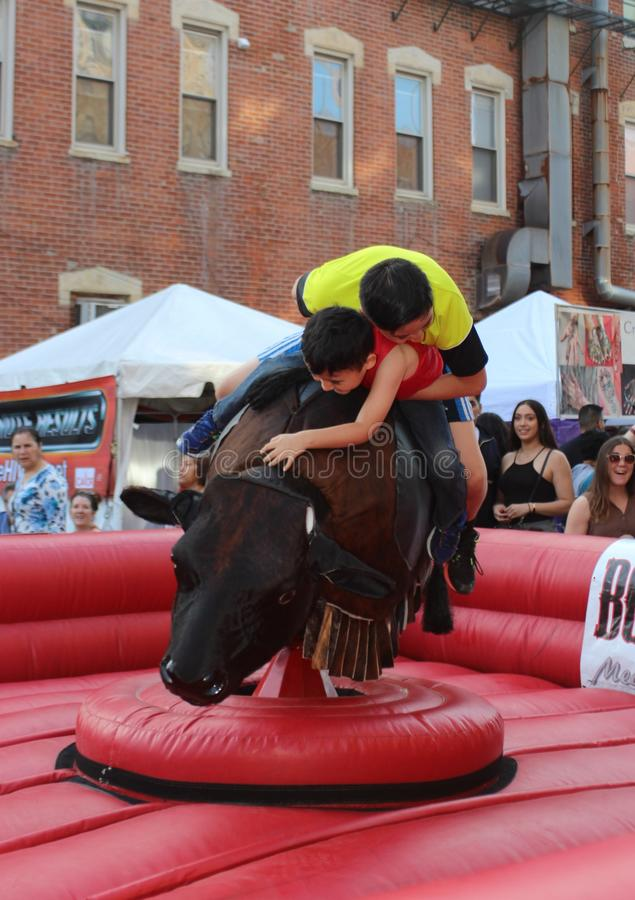 Two Boys Ride Mechanical Bull at Mexican Street Festival in Chicago royalty free stock photography