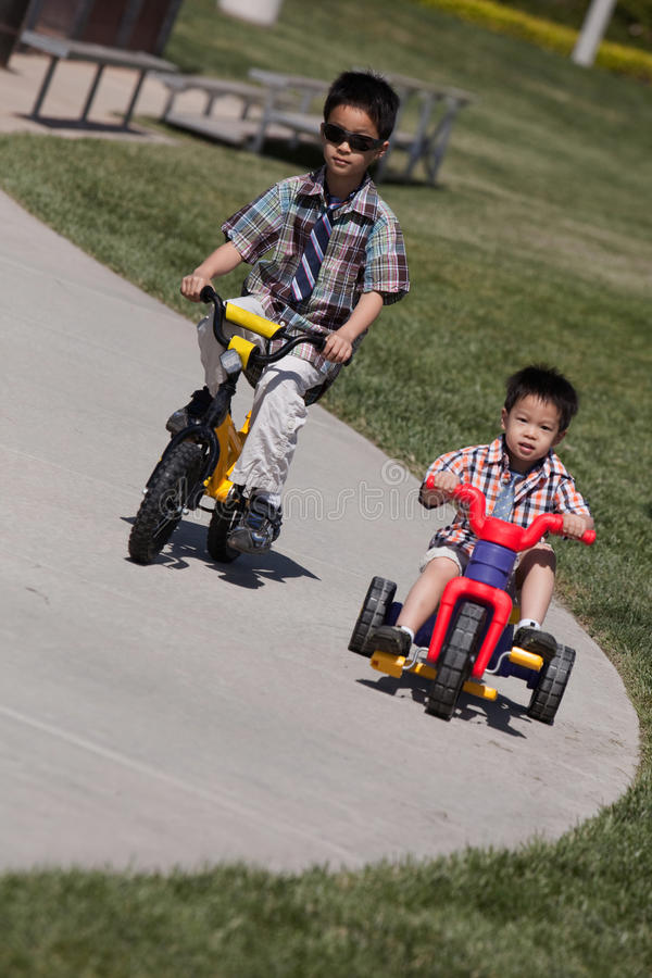 Two boys riding bikes stock photo