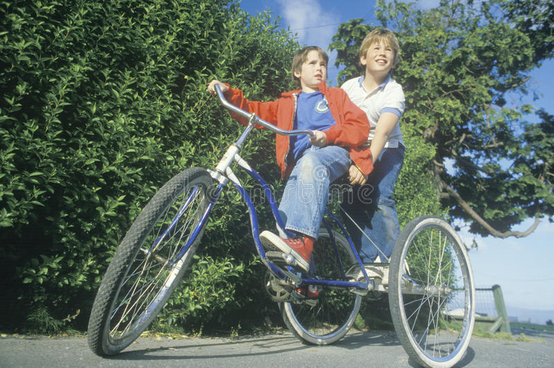 Two boys riding a three wheeled bicycle. Ferndale, CA royalty free stock photos