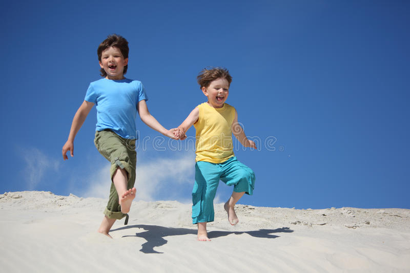 Two boys run on sand stock photography